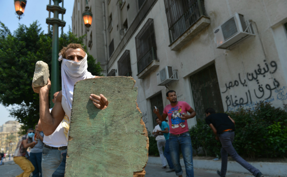 An Egyptian protester holds a makeshift shield as he throws a stone   towards the riot police during clashes near the U.S. embassy in Cairo on   Sept. 13. Police responded by firing tear gas as they clashed with a crowd   protesting against the film, which pokes fun at the   Prophet Mohammed and touches on themes of pedophilia and homosexuality.