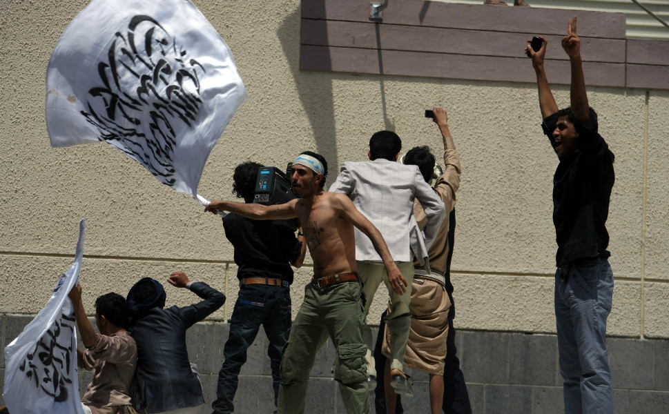 A Yemeni protester waves a flag bearing Islamic calligraphy   outside the gate of the U.S. embassy in Sanaa during a protest over the film on Sept. 13. Yemeni forces drove out  angry protesters who stormed the embassy in the Yemeni capital by  firing warning shots as crowds approached the main gate of the mission.
