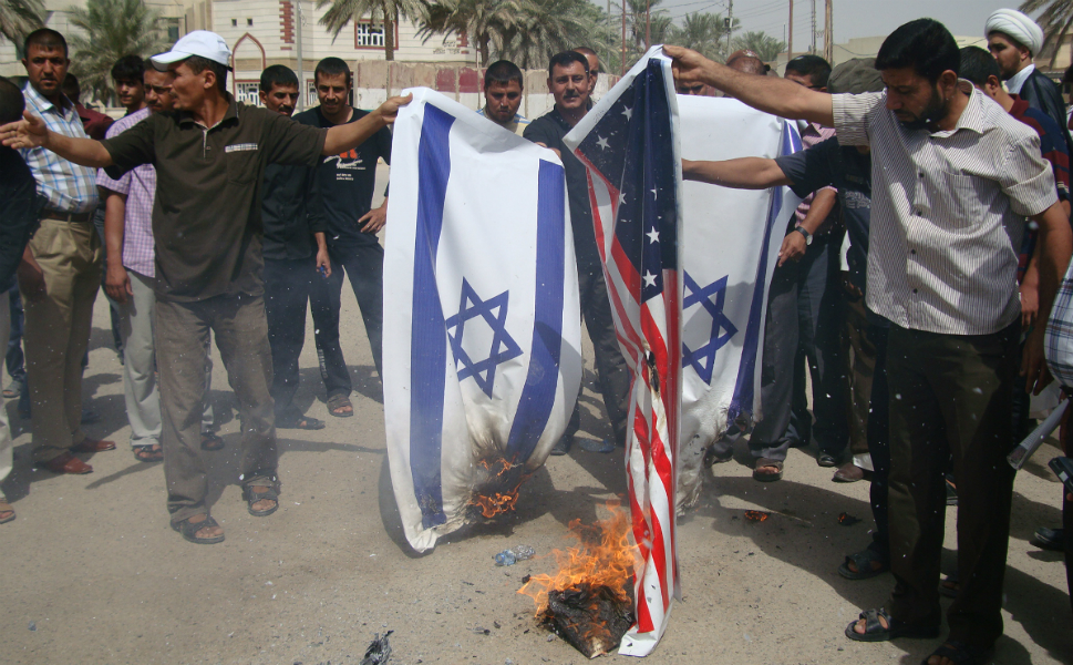 Iraqi supporters of Shiite cleric Moqtada al-Sadr's movement burn the   Israeli and the U.S. flags during a protest denouncing the film on Sept. 13 in the central Iraqi city of   Kut.