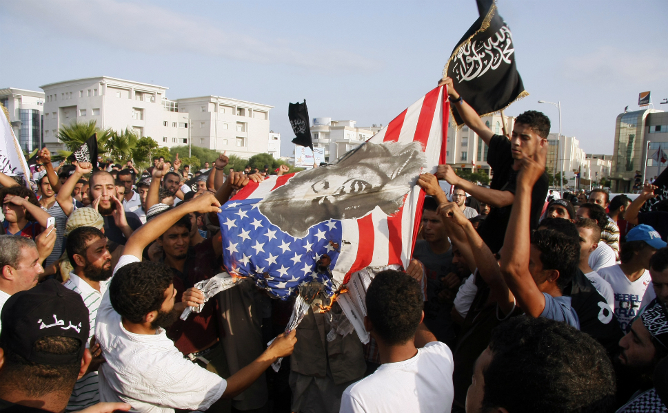 Tunisian protesters burn a U.S. flag bearing a portrait of actress   Marilyn Monroe during a demonstration against the film.