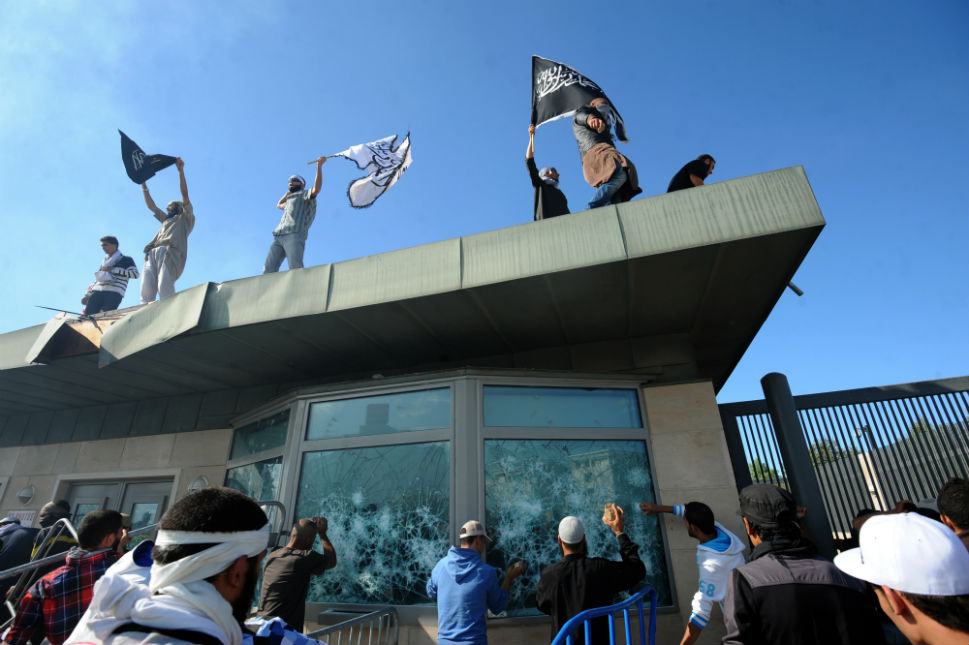Tunisian protesters break the windows as they hold Islamic flags above the gate of U.S. embassy in Tunis during a protest on Sept. 14. Protesters broke into the compound of the U.S. embassy despite volleys of tear gas and warning shots fired by security forces, an AFP photographer reported.