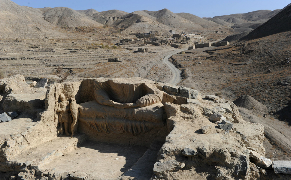 A Buddha statue sits above a road to Mes Anayk on Nov. 23, 2010. The Chinese government-backed mining company gave archaeologists three years to finish the excavations.