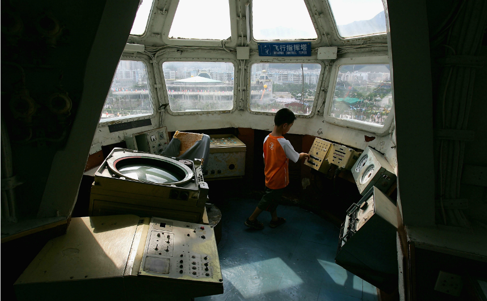 Above, a child explores a control  panel in the control tower of the Minsk.