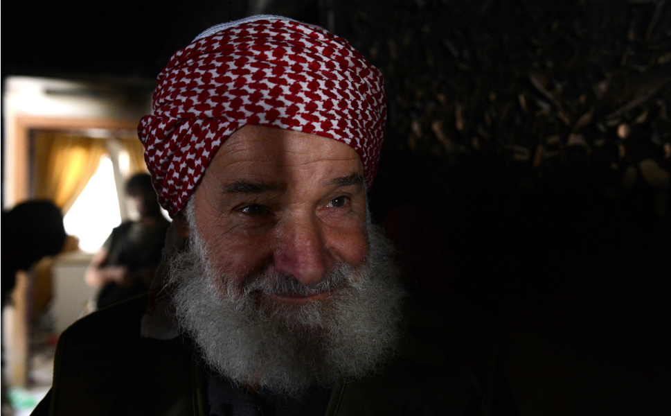 Mohammad Taieb Ismail,  70, stands inside a house from where he is fighting alongside rebel fighters in Aleppo.