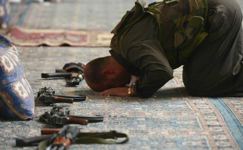 A Syrian rebel commander  prays inside a damaged mosque during the clashes.