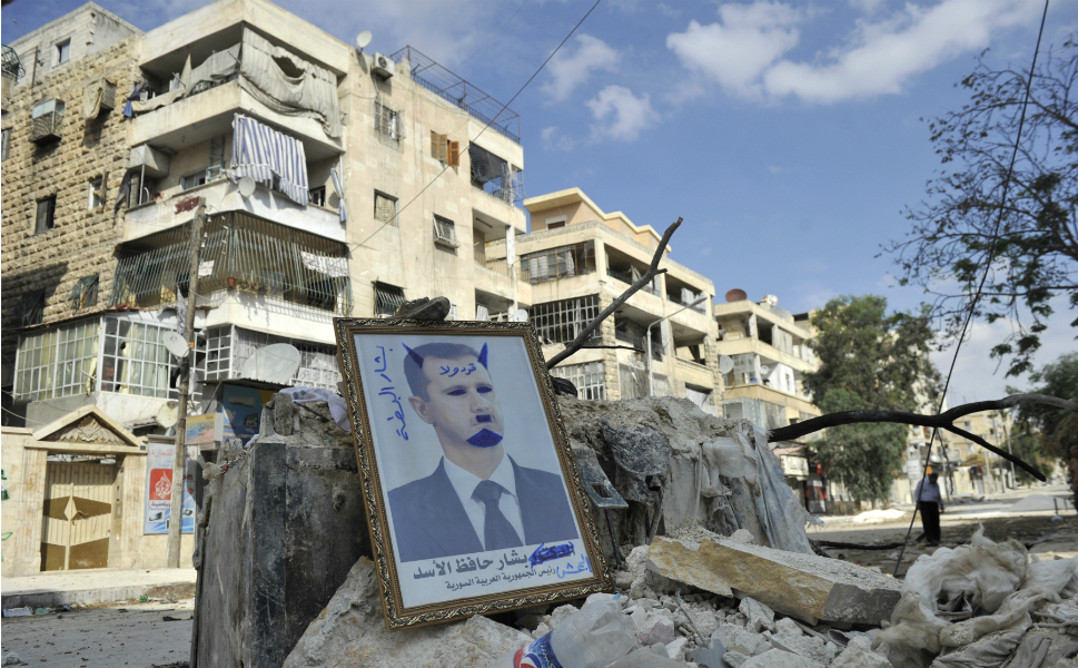 Above, a portrait of Assad defaced to look like a devil is placed on  rubble along a street in Aleppo.