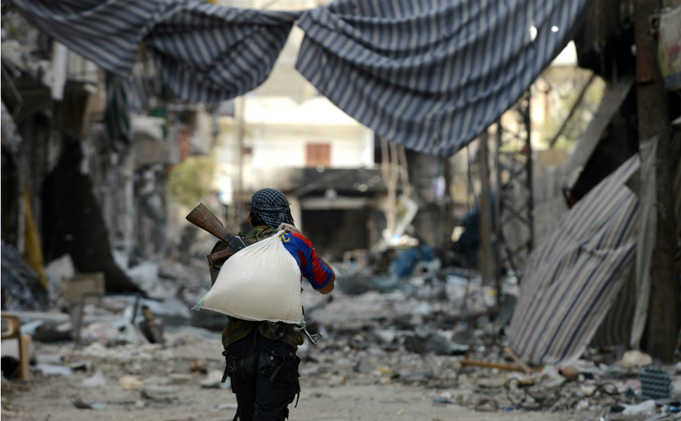 Here, a Syrian rebel carries a sand bag in the Saif al-Dawla district.