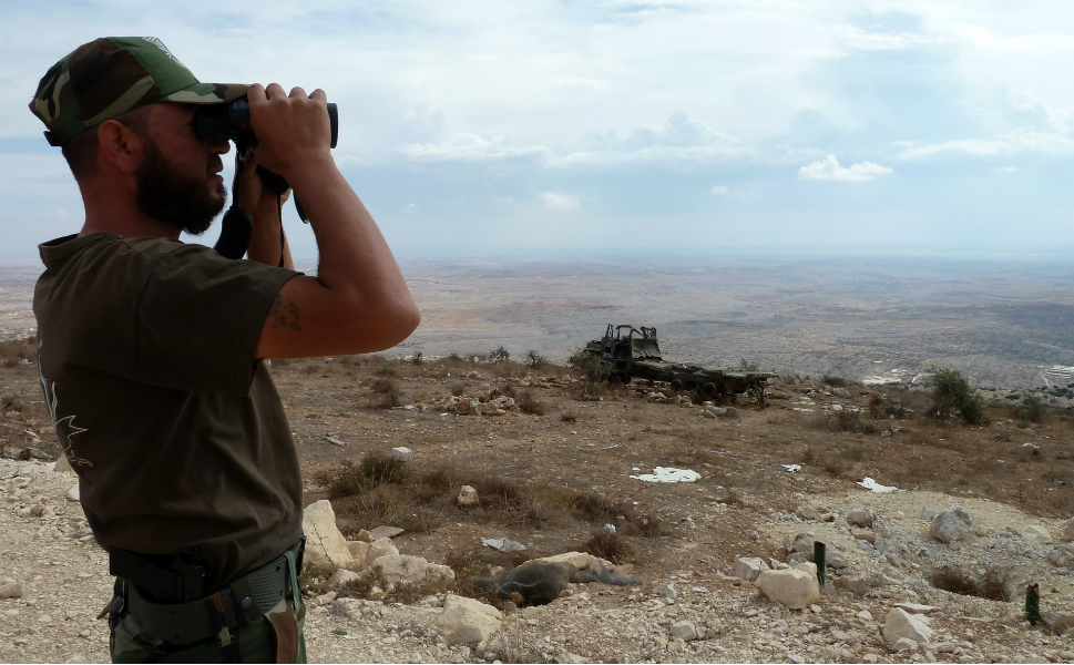A member of the Syrian opposition  uses binoculars to check for regime forces operations from the vantage point of  a former army listening station in the village of Dar Tezzah in the  northwestern province of Idlib. Rebels, who took over the station near Aleppo three months ago, use the strategic  site to monitor the movement of regime forces.