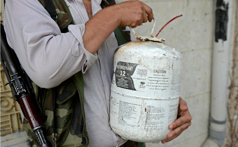 A Syrian rebel carries a  homemade bomb.
