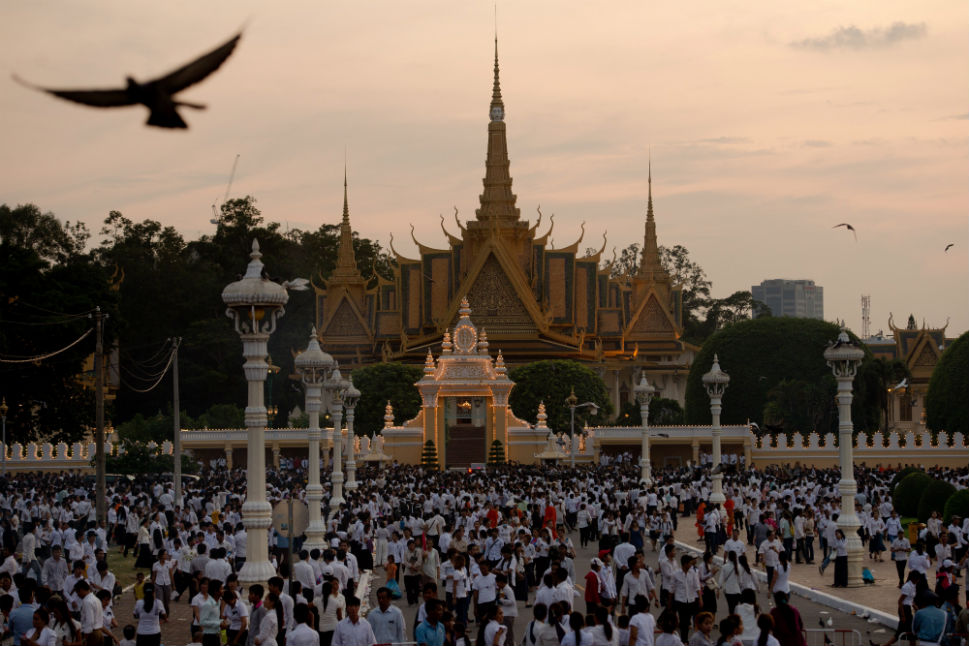 Above, the sun sets as mourners burn incense and offer prayers at the Royal Palace in Phnom Penh onWednesday.