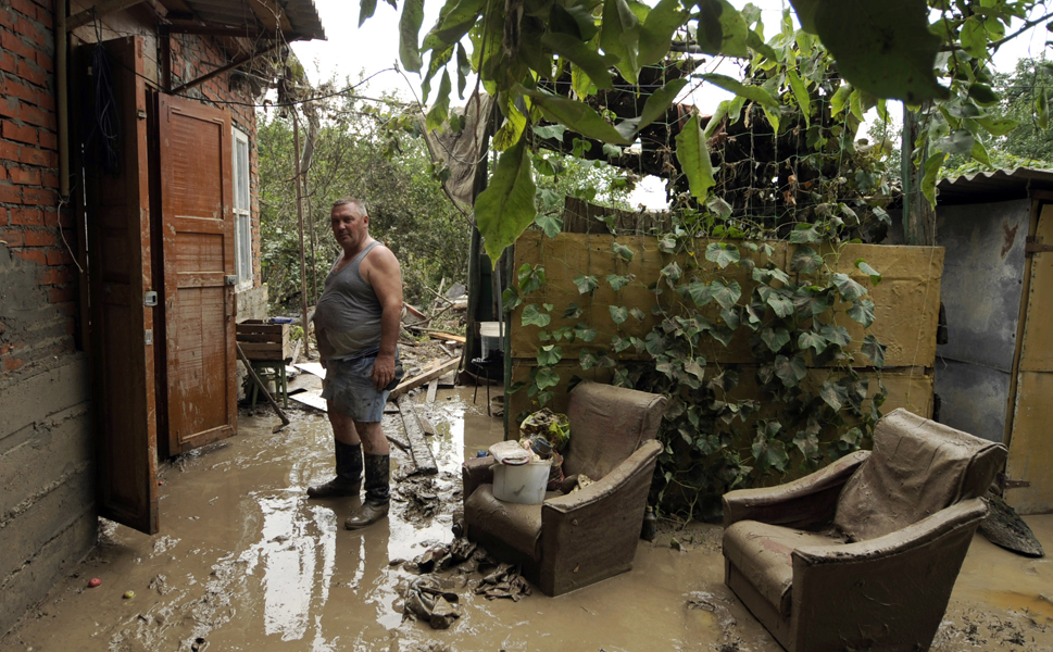 Above, a man stands near his flooded  house in the southern Russian town of Krymsk on July 8. The death toll  from severe flash floods in Russia's southern Krasnodar region reached over 170  people, prompting Russian President Vladimir Putin to order a probe into the government's tardy warnings and emergency response.