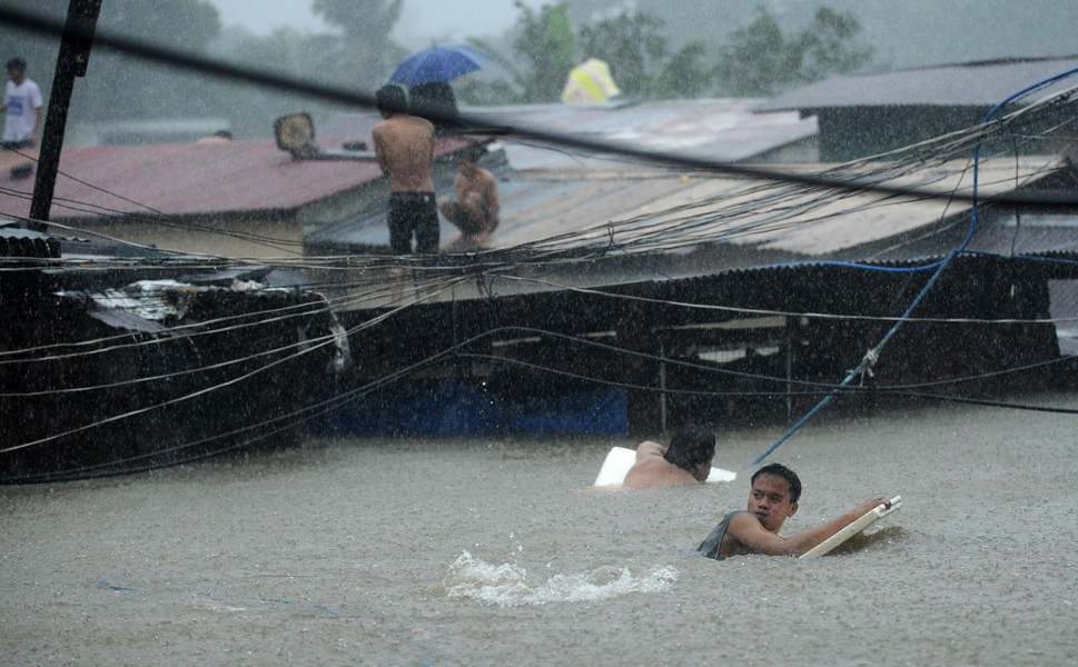 Above, residents try to cross through floodwaters as others wait on the roofs of their houses on Aug. 7 in Manila, Philippines. According to the Office of  Civil Defense, the floods left at least 66 people dead and affected up to 2.68  million people in Manila and surrounding provinces, with more than 440,000  fleeing to evacuation centers.