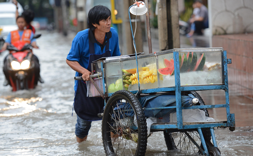 A Thai street food vendor pushes  his cart through a flooded street in Bangkok on Sept. 25. Heavy rains hit  the Thai capital for weeks on end, raising fears of a repeat of last year's  crippling floods, which killed more than 800 people.