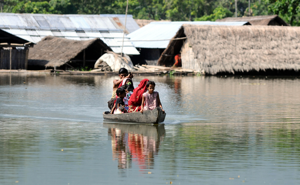 Villagers paddle a boat near  submerged houses in a village near Kaziranga National Park  in northeastern  India on Sept. 27. More than 2 million people were forced from their homes, a problem that was exacerbated by continued rains, which hampered a military air operation to help flood victims. Over 100 people were killed.