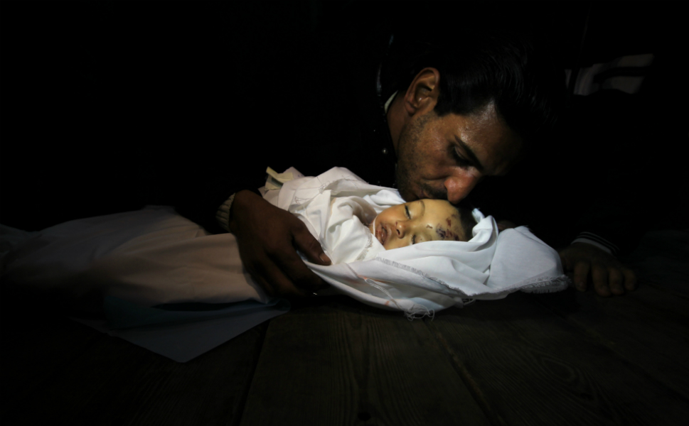 Palestinian relatives mourn over the body of Hanen Tafish, a  10-month-old girl, at the morgue of the al-Shifa hospital in Gaza City on Nov.  15, after she was killed in an Israeli air strike on the Zeitun neighborhood.