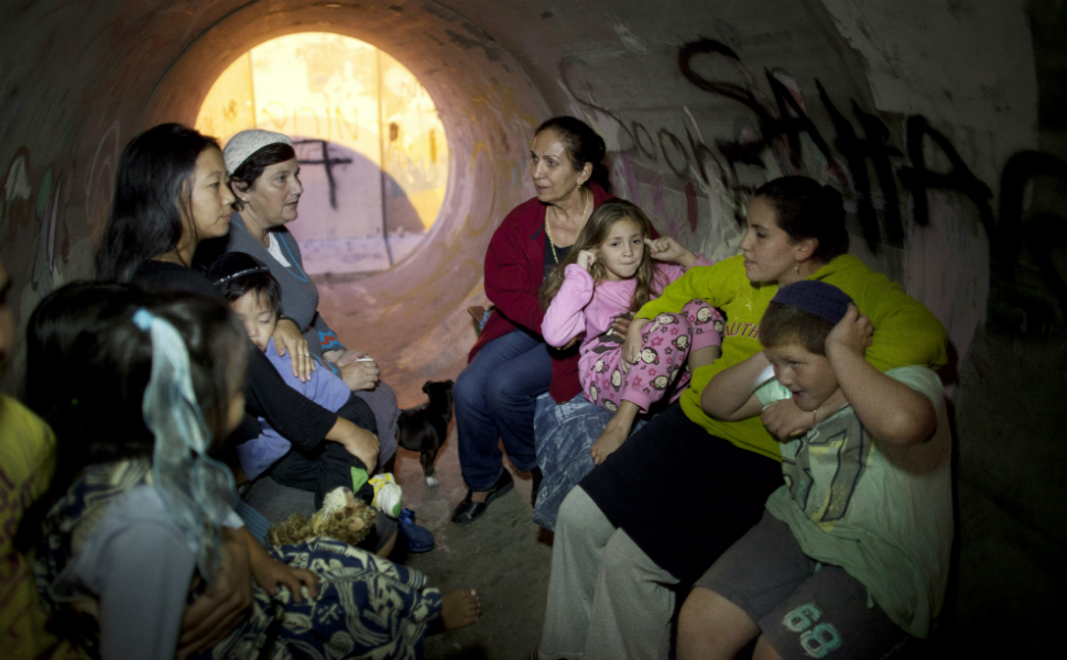 Israelis take cover in a large concrete pipe used as a bomb  shelter after a rocket was launched from the Gaza Strip on Nov. 15 in Nitzan,  Israel. The rocket attack happened some 24 hours after the IDF targeted nearly  200 sites in the Gaza Strip and killed al-Jabari.