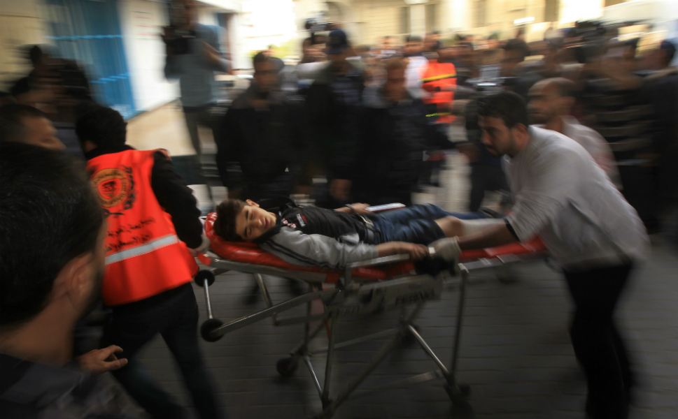 Gaza militants targeted Tel Aviv with another rocket on  Friday, defying Israeli warnings of a possible ground assault to follow its  aerial bombardment of Gaza. Above, Palestinian medical workers wheel a wounded  boy into al-Shifa hospital in Gaza City on Nov. 16.