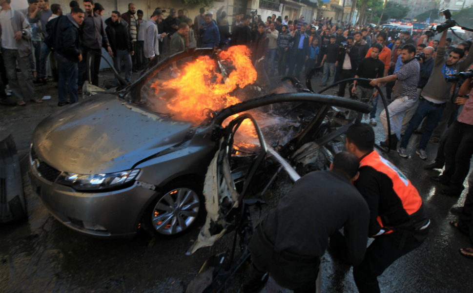 Palestinians attempt to extinguish the fire engulfing  a car belonging to Ahmad al-Jabari, head of Hamas' military wing, after it was  hit by an Israeli air strike in Gaza City on Nov. 14.