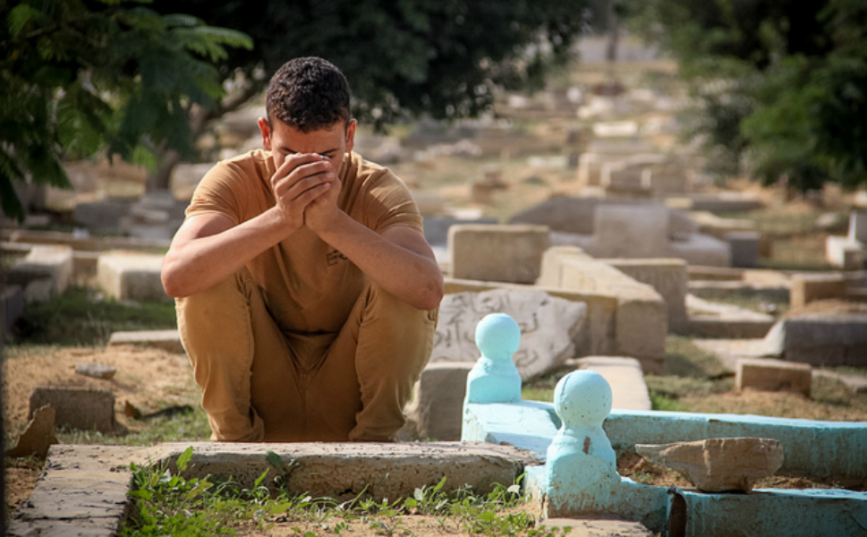 A  Palestinian mourner sits quietly beside a grave in Gaza.