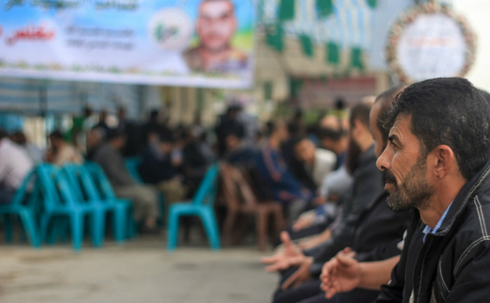 "This is  a ""gathering"" -- they don't like calling it a funeral -- for one of the al-Qassam  fighters [the members of Hamas's military wing]. The fighter's picture is in  the background. After the burial, this is what they do -- all the people gather  together; they eat dates and drink coffee."
