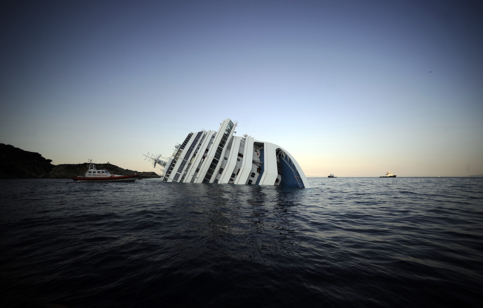 """View of the Costa Concordia on Jan. 14, 2012, after the cruise  ship ran aground and keeled over off the Isola del Giglio. Three people died  and several were missing after the ship with more than 4,000 people on board  ran aground sparking chaos as passengers scrambled to get off. See FP's slide show """"The Life and Death (and Resurrection) of a Cruise Ship.""""       FILIPPO MONTEFORTE/AFP/Getty Images"""