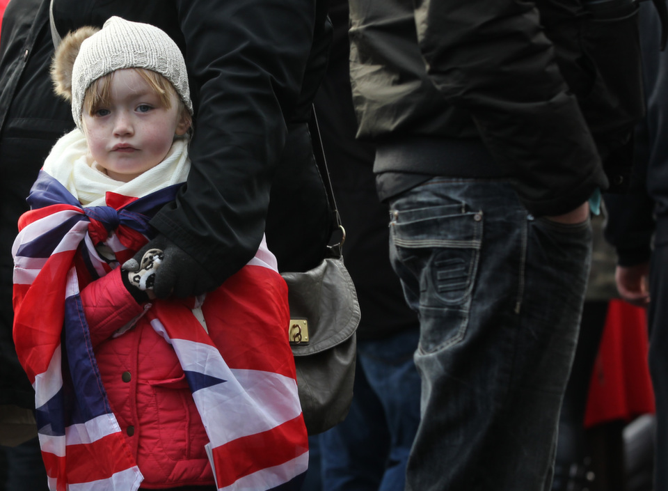 A young child draped in the British Union flag stands with  loyalist protesters during a demonstration outside Belfast City Hall on Jan.  12, 2013, as part of an ongoing campaign opposing Belfast City Council's  decision to restrict the days on which the British Union Flag would fly over the  City Hall.      PETER MUHLY/AFP/Getty Images