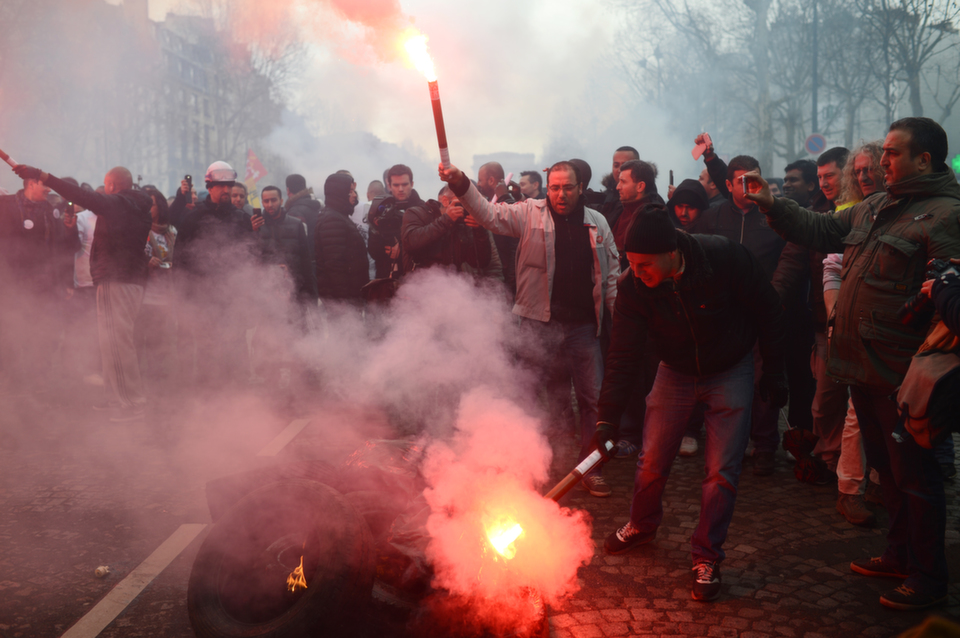 Employees of  French auto giant PSA Peugeot Citroen Aulnay hold flares during a protest on  Mar. 18, 2013 outside PSA headquarters in Paris, where an extraordinary council was being held to present the group's  restructuring plans to trade union representatives.       MARTIN  BUREAU/AFP/Getty Images