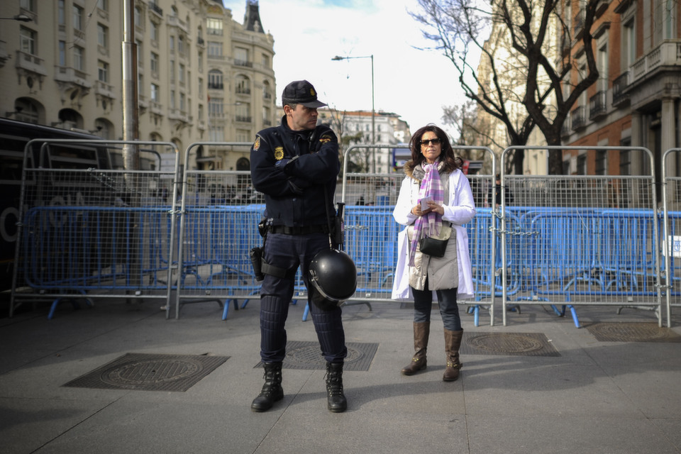 A woman stands behind a police officer during a demonstration of Spanish  health workers against government welfare cuts and privatization plans, in  Madrid on Jan. 13, 2013.       PEDRO ARMESTRE/AFP/Getty Images