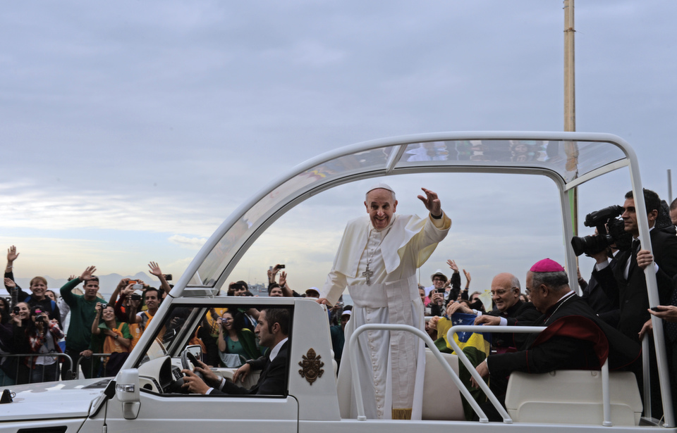 """Pope Francis waves at his followers, as they stand along the  beachfront in Rio de Janeiro awaiting mass on July 28, 2013. Foreign Policy named Pope Francis a 2013 Global  Thinker -- for bringing  """"the freshness of the gospel to the Catholic Church.""""      A note to readers, some of the following images contain graphic content.       EVARISTO SA/AFP/Getty Images"""