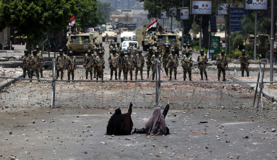 """Two veiled Egyptian women, supporters of deposed president Mohamed  Morsy, sit in front of police blocking access to the headquarters of  the Republican Guard in Cairo on July 8, 2013. In the months since Morsy's ouster, Egypt has quieted down but, as Eric Trager writes in """"Clan Warfare,"""" the country's relative calm will be shortlived because """"[t]he new regime has done nothing to address the factors that catalyzed the first uprising almost three years ago,"""" he wrote.      MAHMUD HAMS/AFP/Getty Images"""