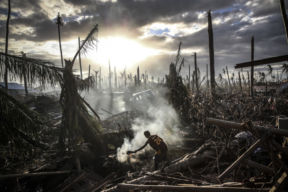 """A man fans a fire  on Nov. 19, 2013 in Leyte, Philippines. Typhoon Haiyan which ripped through  the Philippines in October has been described as one of the most powerful  typhoons ever to hit land, leaving thousands dead and hundreds of thousands  homeless. Countries all over the world have pledged relief aid to help support  those affected by the typhoon but as FP's Catherine Traywick wrote in November, early relief efforts proved """"anugly introduction to the personality-centered world of Philippine politics, one marked by feuding dynasties, rampant cronyism, and, above all, dysfunction.""""      Dan Kitwood/Getty Images"""