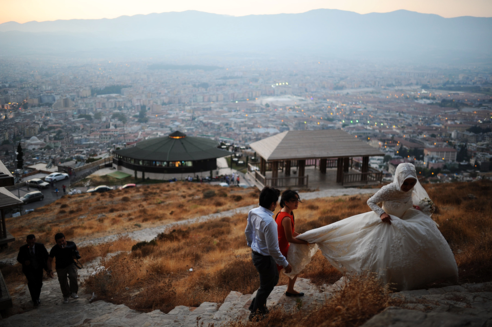 A newly married  couple walks up a hill with a view of the city of Antakya, on Aug. 29, 2013.       BULENT  KILIC/AFP/Getty Images