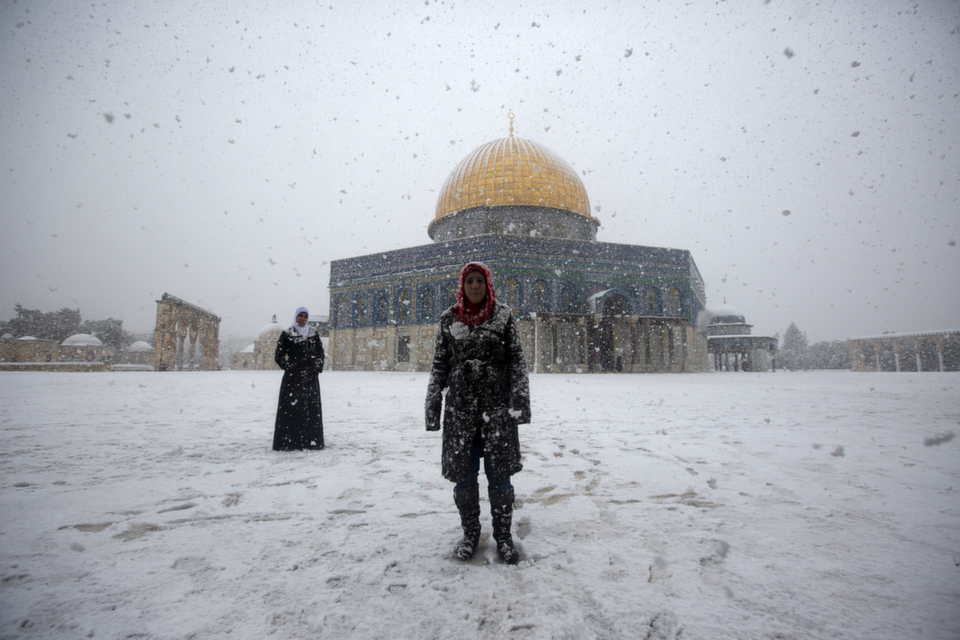 """Two Palestinian women stand in front of the Dome of the Rock at  the Al-Aqsa mosques compound in Jerusalem on Dec. 12, 2013. A bruising winter  storm brought severe weather to the Middle East, forcing the closure of roads  and schools and blanketing much of the high altitude areas with snow and ice. See Foreign Policy's slide show, """"Snow in the Desert"""" featuring photos of extreme weather in the Middle East.      AHMAD GHARABLI/AFP/Getty  Images"""