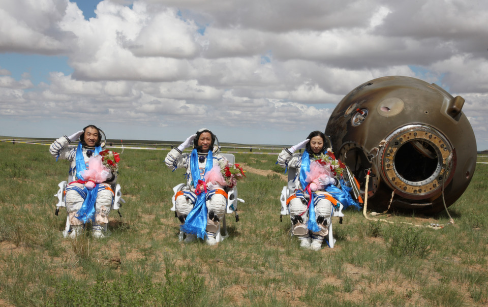 """Chinese astronauts Zhang Xiaoguang, Nie Haisheng, and Wang Yaping  salute after getting out of the re-entry capsule of China's Shenzhou X  spacecraft following its successful on June 26, 2013 in the Inner Mongolia Autonomous  Region of China. The astronauts returned after a 15-day trip to a prototype  space station. See FP's slide show about China's space program, """"Houston, We Have a Problem.""""       ChinaFotoPress/Getty Images"""