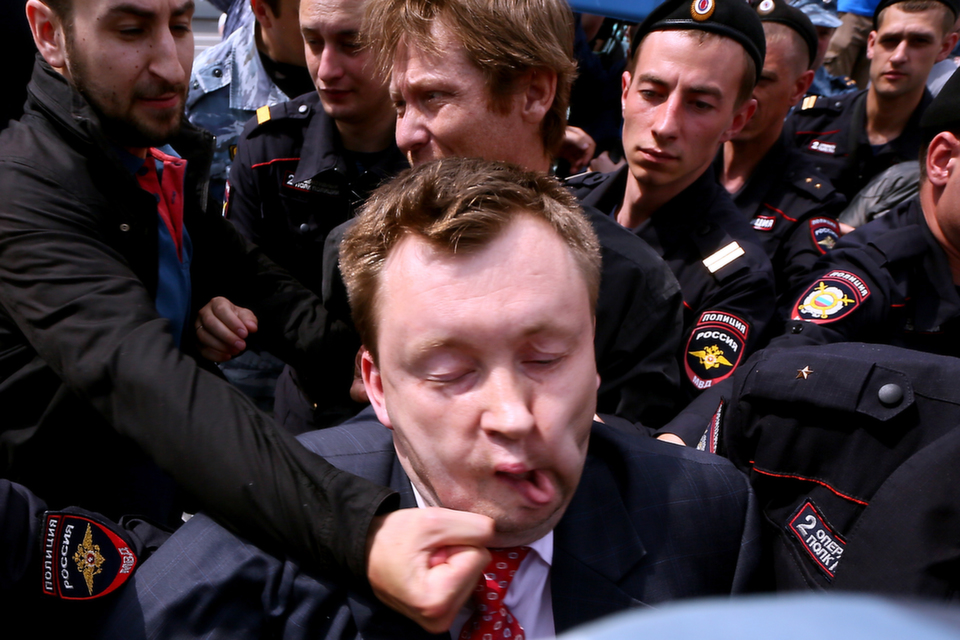 """Unknown anti-gay activist hits Russia's gay and LGBT rights  activist Nikolai Alexeyev (center) during an unauthorized gay rights rally in  central Moscow on May 25, 2013. Moscow city authorities had previously rejected  requests for a gay rights rally, but  Alexeyev said he would fight a ban in court. In June, President Vladimir Putin signed a law prohibiting""""propaganda  of nontraditional sexual relations to minors."""" The furor, accordingto Democracy Lab's Prachi Vidwans, has prompted many  politicians to avoid or boycott  the 2014 Olympics, to be held in Sochi, Russia.      ANDREY SVITAILO/AFP/Getty Images"""