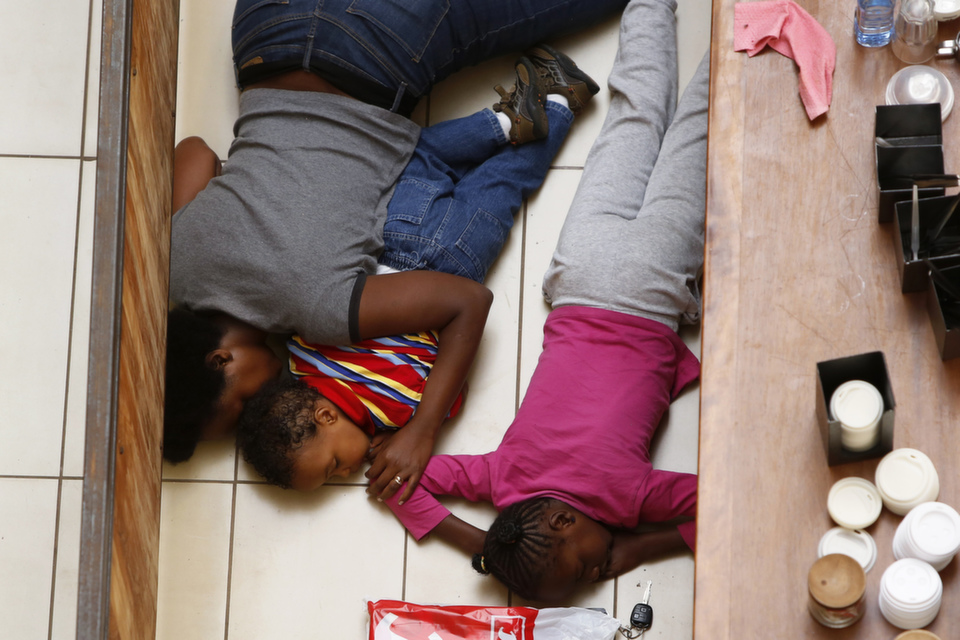 A mother and her children hide from gunmen at  Westgate Shopping Centre in Nairobi Sept. 21, 2013. Gunmen stormed the  shopping mall in Nairobikilling39 people, and injuring 150 others. Sporadic gun shots could be heard  hours after the assault started, as soldiers surrounded the mall and police and  soldiers combed the building, hunting down the attackers shop by shop.Somali militant group al-Shabab later claimed responsibility for the attack.      REUTERS/Siegfried Modola