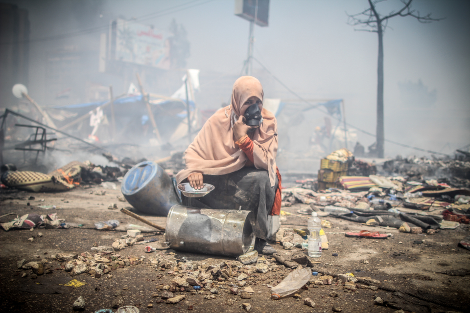 A protester sits  holding cooking pots sits amid the rubble of one of two sit-ins organized  by supporters of the ousted President Mohamed Morsy, near Rabaa Adawiya mosque, in Cairo on  Aug. 14, 2013.      Mosa'ab  Elshamy/FlickrVision