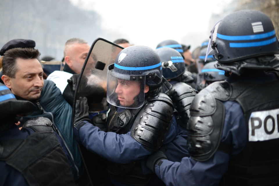 Anti-riot policemen face employees of the French auto giant Peugeot  Citroen Aulnay's plant during a protest on Mar. 18, 2013 in Paris.      MARTIN BUREAU/AFP/Getty Images