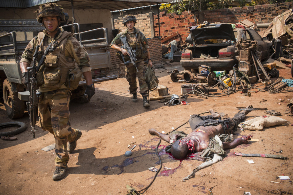 French  soldiers pass the body of a Muslim man killed, then mutilated, in the streets of Bangui's Combatan quarter, on Jan. 29.       Marcus Bleasdale/VII