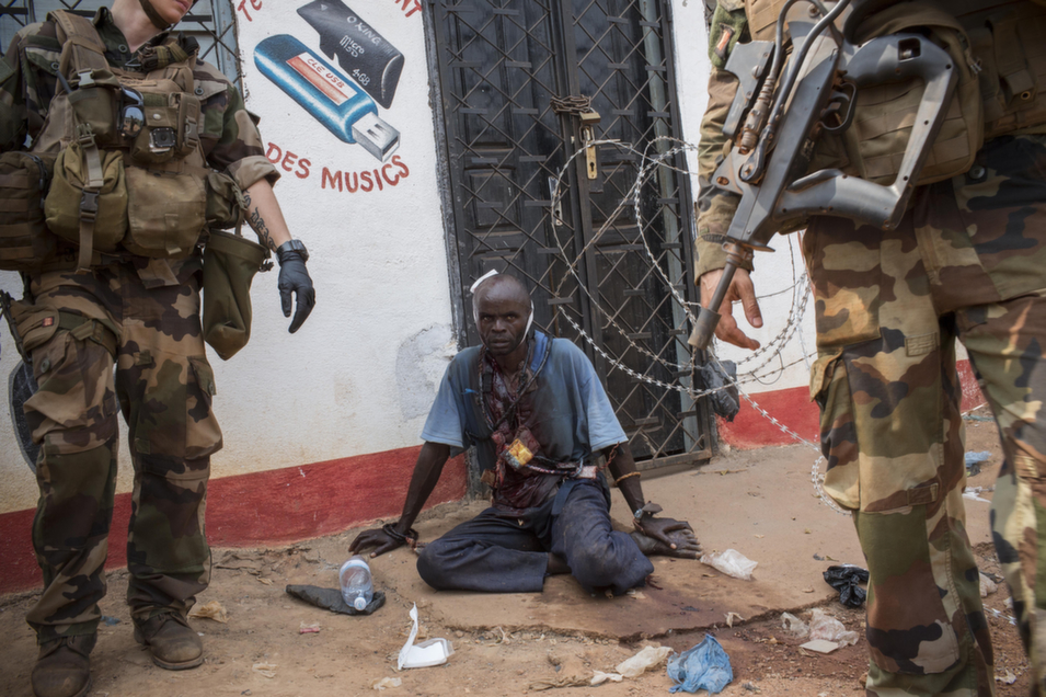 An anti-balaka fighter sits on the ground in Bangui on Jan. 23, after being slashed by a machete. He  remained under the care of French soldiers until the Red Cross was able to  evacuate him. The day after this image was taken, in the same neighborhood, anti-balaka killed a Seleka  fighter who had left his encampment in search of food.       Marcus Bleasdale/VII