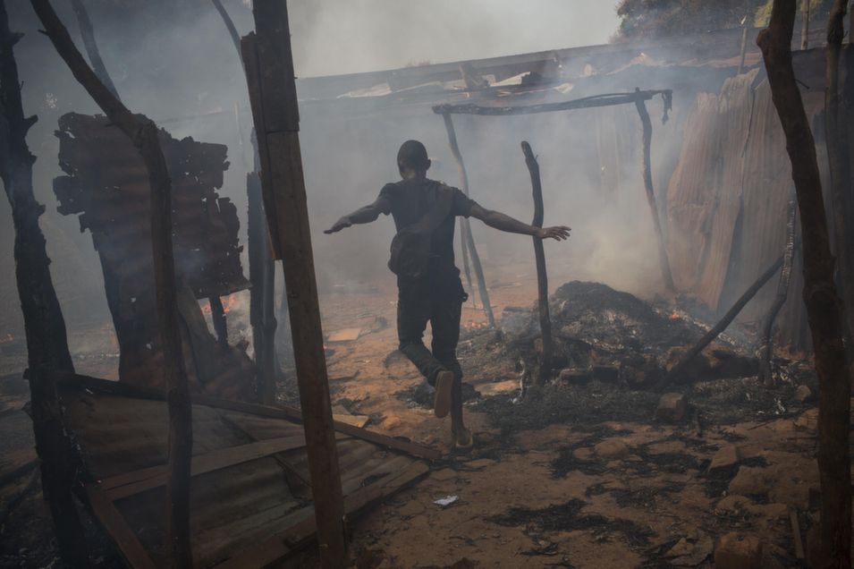 On Jan. 23, a young man runs through the looted and burning homes of Muslims in the PK13 quarter, located on  the outskirts of Bangui.       Marcus Bleasdale/VII