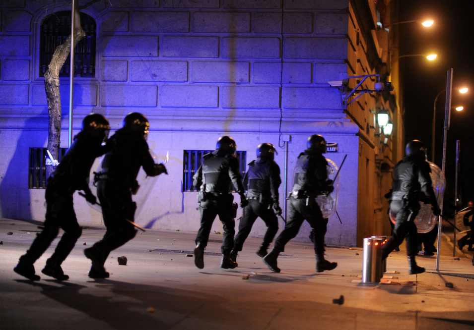 """Riot police charge  protesters after the """"Marches for Dignity"""" protest ended with violent clashes  between police and youths in Madrid, on March 22. Demonstrators had converged on  the Spanish capital from several Spanish regions in an  attempt to highlight the plight of the poor.       Denis Doyle/Getty Images"""