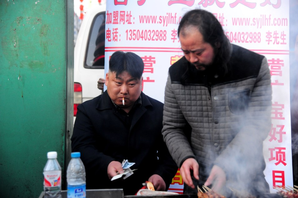 This picture taken on  March 22 shows a Chinese street food vendor (seen on the left), who bears a striking resemblance to North  Korean leader Kim Jong-Un, sitting by his barbecue stall in Shenyang, northeast  China's Liaoning province. Though the man's identity remains unknown, he works in the  northeastern Chinese city of Shenyang, not far from the border with North  Korea.       STR/AFP/Getty Images