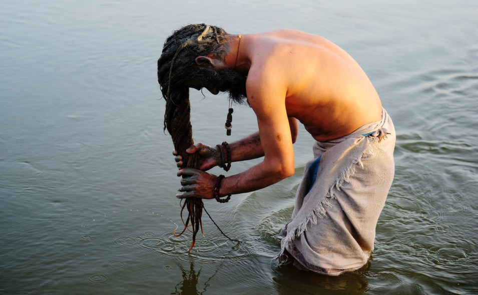 """An Indian """"sadhu,"""" or  holy man, washes his hair with mud at Sangam, the confluence of the rivers  Ganges, Yamuna, and the mythical Saraswati in Allahabad, on March 22.      Sanjay Kanojia/AFP/Getty  Images"""