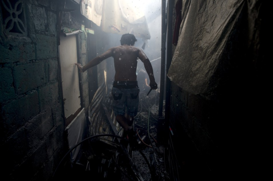 A resident walks among  debris after a fire that razed a slum area in Manila on March 22.       NOEL CELIS/AFP/Getty  Images