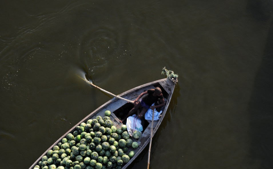 An Indian laborer  transports pumpkins on a boat at Fafamau village near Allahabad on March 26.      Sanjay Kanojia/AFP/Getty  Images