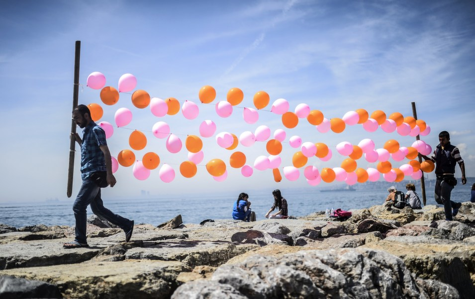 Men carry balloons near the sea at Kadikoy on May 3, in  Istanbul.      BULENT KILIC/AFP/Getty Images