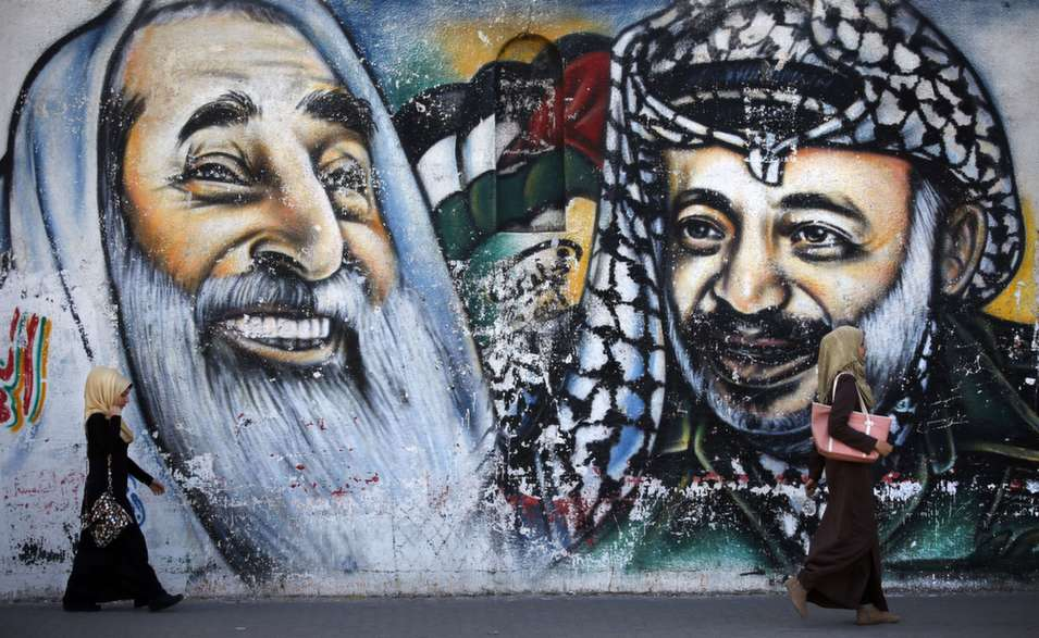 Palestinian women walk past a mural depicting late Hamas  spiritual leader Sheikh Ahmed Yassin (seen left) and late Palestinian leader Yasser  Arafat on May 4, in Gaza City. The Hamas movement's deputy leader Musa Abu Marzouq said the Islamist movement will never recognise Israel and will not  accept the conditions laid out by the Middle East peacemaking quartet.       THOMAS COEX/AFP/Getty Images