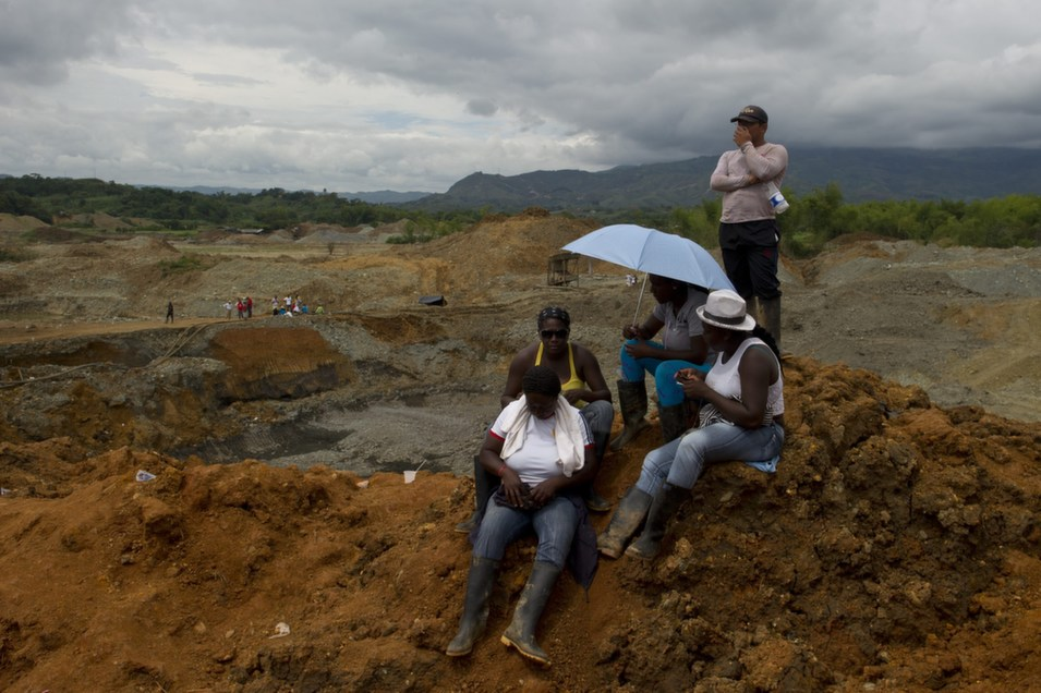 Miners watch as rescue workers attempt to remove sludge looking  for victims of a gold mine on May 3, in San Antonio, Colombia. The mine  collapsed on May 1 while independent mine workers were excavating it without  authorization. At least 12 miners are dead, according to the New York Times.       LUIS ROBAYO/AFP/Getty Images