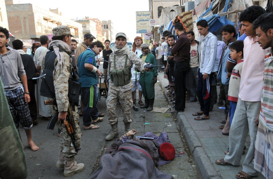 Yemeni soldiers and citizens stand around the body of Yemeni  army commander Mohammed Guawza who was shot four times while walking down a  street in the capital Sanaa early in the morning on May 5, by two armed men  suspected to be members of al-Qaeda.       STR/AFP/Getty Images
